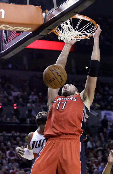 Toronto Raptors center Jonas Valanciunas, from Lithunia, scores and is fouled by Portland Trail Blazers guard Mo Williams during the first half of an NBA basketball game in Portland, Ore., Saturday, F