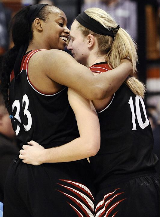 Cincinnati seniors Jeanise Randolph, left, and Kayla Cook embrace after they finish playing in the second half of an NCAA college basketball game against Connecticut in the quarterfinals of the Americ