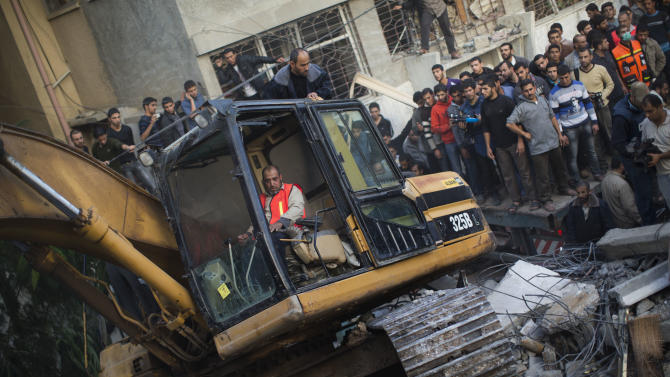Palestinians watch bulldozers remove debris from the Daloo family house following an Israeli air strike in Gaza City, Sunday, Nov. 18, 2012. An Israeli missile flattened a two-story house in a residential neighborhood of Gaza City on Sunday, killing several civilians shortly after Israel announced plans to intensify an offensive by attacking the homes of wanted militants, medical officials said. Gaza health official Ashraf al-Kidra says several women, including an 80-year-old women, and several small children were among the dead. (AP Photo/Bernat Armangue)