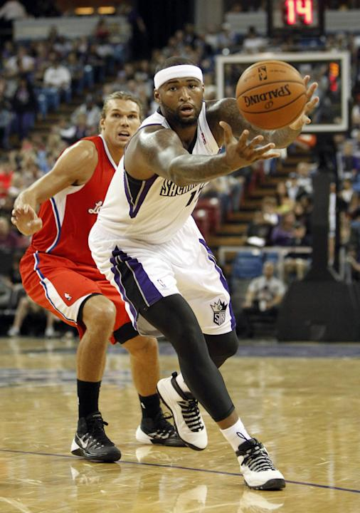 Sacramento Kings center DeMarcus Cousins, right, goes after the ball as Los Angeles Clippers  forward Lou Amundson, left, looks on during the third quarter of an NBA preseason basketball game in Sacra