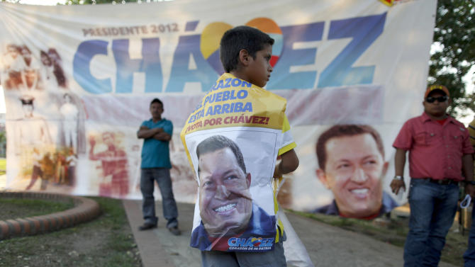 A a boy stands in front of a banner of late President Hugo Chavez at the main square of his hometown,  Sabaneta, in western Venezuela, Friday, March 8, 2013. Chavez died on March 5 after a nearly two-year bout with cancer. He was 58. (AP Photo/Esteban Felix)