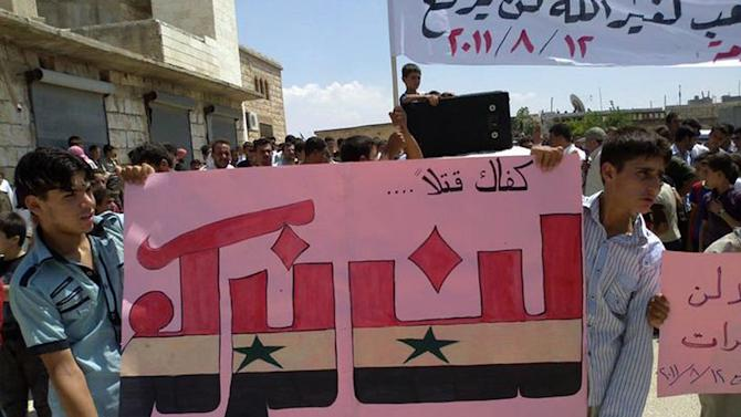 """In this citizen journalism image made on a mobile phone and provided by Shaam News Network, Anti-Syrian President Bashar Assad protesters hold up an Arabic banner reading:""""Enough killing,  will not bow,"""" during a demonstration against the Syrian regime, at Maarat Harma village, in Edlib province, northern Syria, on Friday Aug. 12, 2011. Tens of thousands of Syrian protesters shouted for President Bashar Assad's death Friday in a dramatic escalation of their rage and frustration, defying bullets and rooftop snipers after more than a week of intensified military assaults on rebellious cities, activists and witnesses said. Security forces killed at least 14 protesters, according to human rights groups. (AP Photo/Shaam News Network) EDITORIAL USE ONLY, NO SALES, THE ASSOCIATED PRESS IS UNABLE TO INDEPENDENTLY VERIFY THE AUTHENTICITY, CONTENT, LOCATION OR DATE OF THIS HANDOUT PHOTO"""