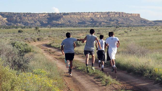 In this Friday, Oct. 13, 2013 photo, members of the Hopi High School boys cross-country team head down a trail near Polacca, Ariz., for practice. It is the earth that their Hopi ancestors ran long distances for centuries in prayer for rain, prosperity and all of mankind. These boys are driven by competition. The team leads the nation in consecutive state title wins with 23. (AP Photo/Felicia Fonseca)