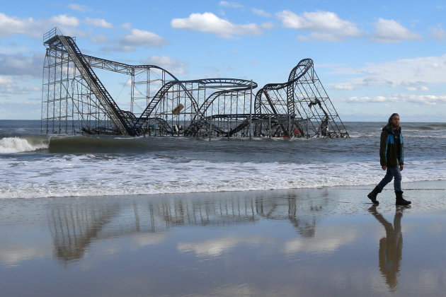 ohn Okeefe walks on the beach as a rollercoaster that once sat on the Funtown Pier in Seaside Heights, N.J., rests in the ocean on Wednesday, Oct. 31, 2012 after the pier was washed away by superstorm Sandy