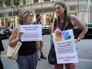 "Demonstrators gather with signs outside the New York NBC studios in Manhattan, on August 13, to protest the debut of a new reality show which they say presents war as a ""game."" The show, ""Stars Earn Stripes,"" is hosted by former NATO commander Wesley Clark, and pits celebrities paired with servicemen who face each other in missions inspired by real military maneuvers"