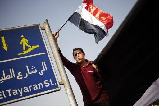 An Egyptian protester waves the national flag outside the Ministry of Defense in Cairo on July 3, 2013