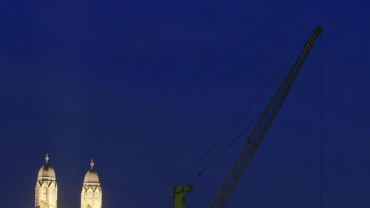 A night view shows a dockside crane on the banks of the Limmat river in Zurich