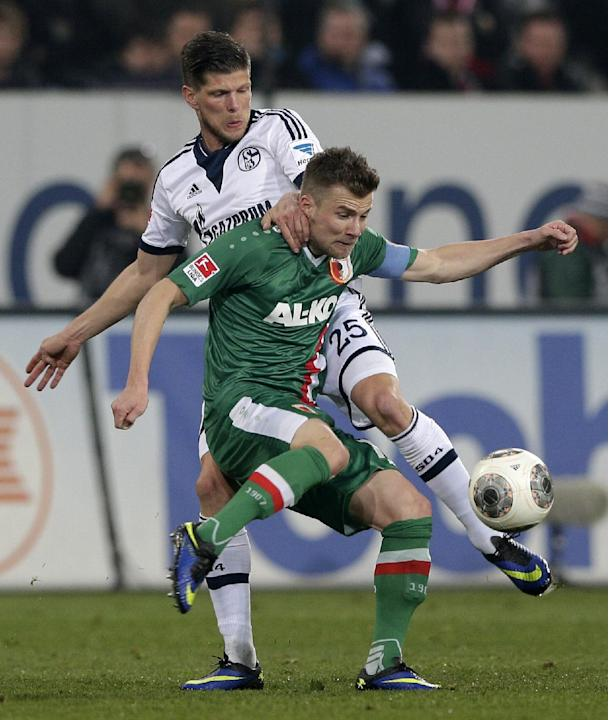 Schalke's Klaas-Jan Huntelaar of the Netherlands, background, and Augsburg's Daniel Baier challenge for the ball during the German first division Bundesliga soccer match between FC Augsburg an