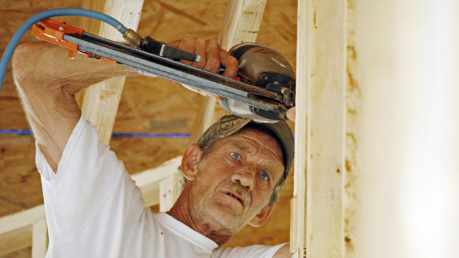 In this Friday, June 1, 2012, photo, John Knight uses an air hammer as he frames a new house on this lot in the Patrick Farms community  in Pearl, Miss. Confidence among U.S. builders ticked up in June to a five-year high, an indication that the housing market is slowly improving. (AP Photo/Rogelio V. Solis)