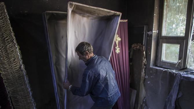 A man carries out a coffin from an undertaker's showroom that was recently shelled in Donetsk, eastern Ukraine