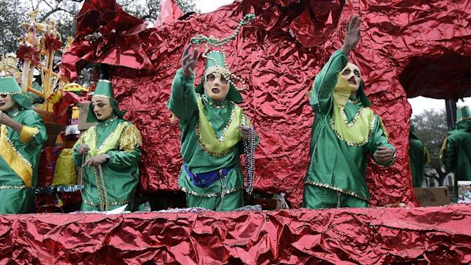 Carnival riders throw beads from a  float during the Krewe of Mid-City Mardi Gras parade in New Orleans, Sunday, Feb. 10, 2013. (AP Photo/Gerald Herbert)