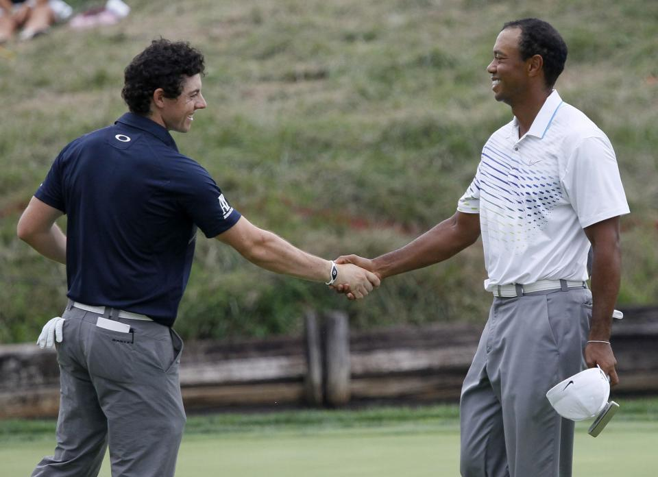 Rory McIlroy, left, of Northern Ireland, shakes hands with Tiger Woods after they both birdied the 18th hole during the second round of the BMW Championship PGA golf tournament at Crooked Stick Golf Club in Carmel, Ind., Friday, Sept. 7, 2012. (AP Photo/Charles Rex Arbogast)