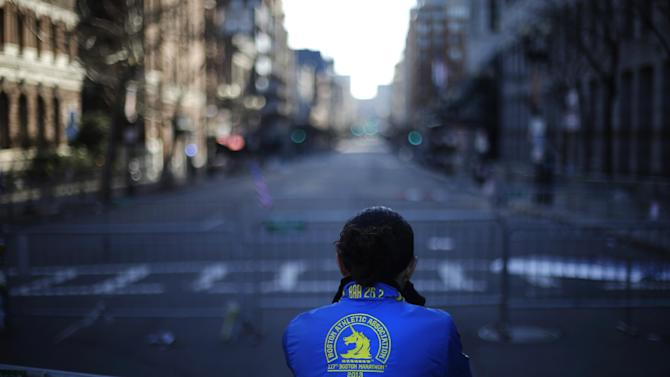 Lizzie Lee of Lynnwood, Wash., pauses near the finish line of Monday's Boston Marathon explosions, which killed at least three and injured more than 140, Thursday, April 18, 2013, in Boston. Lee said she almost completed the marathon before the blasts. (AP Photo/Matt Rourke)