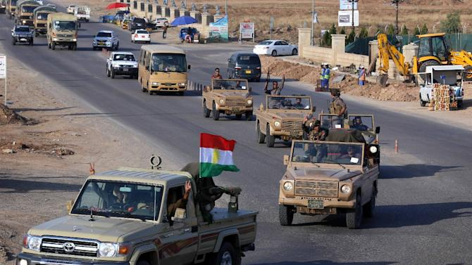 Kurdish peshmerga fighters drive in convoy through Arbil after leaving a base in northern Iraq on October 28, 2014 headed for the Syrian town of Kobane