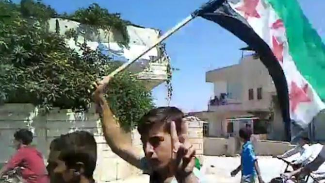 In this image made from amateur video released by the Shaam News Network and accessed Wednesday, July 18, 2012, a Syrian boy flashes the victory sign during a celebration after hearing about the suicide attack that hit the National Security building in Idlib, north Syria. A bomb ripped through a high-level security meeting Wednesday in Damascus, killing the defense minister as well as President Bashar Assad's brother-in-law in the harshest blow to the government's inner circle in the 16-month uprising. (AP Photo/Shaam News Network via AP video) TV OUT, THE ASSOCIATED PRESS CANNOT INDEPENDENTLY VERIFY THE CONTENT, DATE, LOCATION OR AUTHENTICITY OF THIS MATERIAL