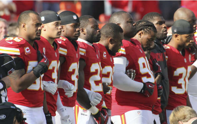 Kansas City Chiefs players stand arm-in-arm during a moment of silence before an NFL football game against the Carolina Panthers at Arrowhead Stadium in Kansas City, Mo., Sunday, Dec. 2, 2012. (AP Pho