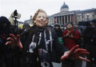 A woman wearing a mask representing late former British prime minister Margaret Thatcher poses for photographers at a party to celebrate Thatcher's death at Trafalgar Square in central London April 13, 2013. REUTERS/Olivia Harris