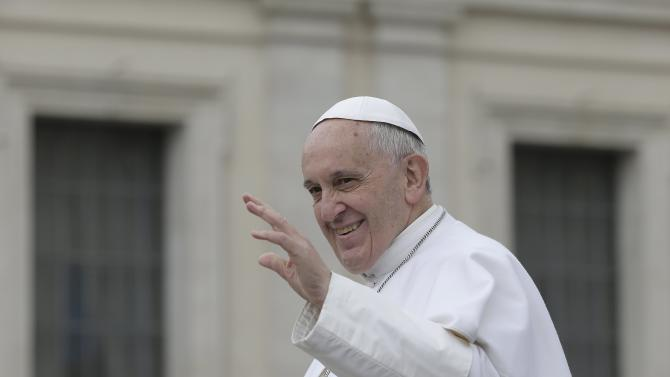 Pope Francis waves as he leaves at the end of the general audience in Vatican