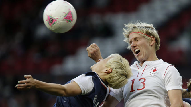 United States' Megan Rapinoe, left, heads for the ball against Canada's Sophie Schmidt, right, during their semifinal women's soccer match between the USA and Canada at the 2012 London Summer Olympics, in Manchester, England, Monday, Aug. 6, 2012. (AP Photo/Hussein Malla)