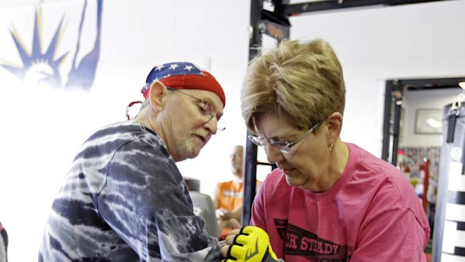 In this photo taken March 19, 2013, Sue Burton, right, helps Dave Beery don his gloves as he prepares to box during a workout at Rock Steady Boxing in Indianapolis. Rock Steady boxing is a unique nonprofit gym that, since 2006, has offered a uniquely effective form of physical exercise to people who are living with Parkinson's. (AP Photo/Michael Conroy)