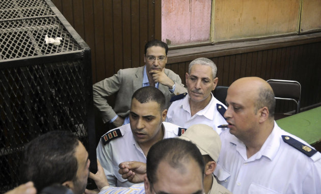 "Islam Afifi, the chief editor of el-Dustour newspaper, center, attends a court hearing in Cairo, Egypt, Thursday, Aug. 23, 2012. A Cairo court on Thursday ordered the chief editor of an Egyptian newspaper detained pending trial on charges of insulting the country's president and ""spreading lies."" The case against Afifi of the privately-owned el-Dustour daily is one of several lawsuits brought mainly by Egypt's Islamists against journalists, accusing them of inflammatory coverage and inciting the public against the Muslim Brotherhood, the country's largest political group."