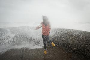 A woman is soaked as large waves crash against the…