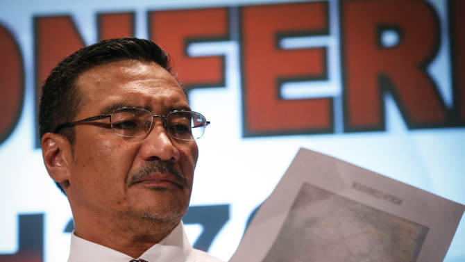 Malaysia's acting Transport Minister Hishamuddin Hussein looks on a map of a search corridor during a press conference at a hotel near the Kuala Lumpur International Airport, in Sepang, Malaysia, Monday, March 17, 2014. Twenty-six countries are involved in the massive international search for the Malaysia Airlines jetliner that disappeared on March 8 with 239 people aboard. They include not just military assets on land, at sea and in the air, but also investigators and the specific support and assistance requested by Malaysia, such as radar and satellite information. (AP Photo/Vincent Thian)
