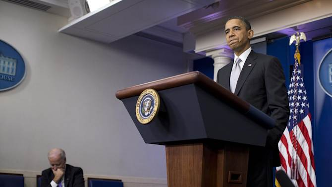 Vice President Joe Biden, left, listens as President Barack Obama pauses during remarks on the the fiscal cliff negotiations during a news conference in the briefing room of the White House on Wednesday, Dec. 19, 2012 in Washington.  Obama also announced that Biden will lead an administration-wide effort to curb gun violence in response to the Connecticut school shooting. (AP Photo/ Evan Vucci)
