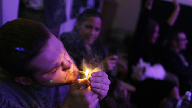 A man smokes marijuana on the official opening night of Club 64, a marijuana-specific social club, where a New Year's Eve party was held, in Denver, Monday Dec. 31, 2012. On Election Day, Nov. 6, 2012, a plurality of Coloradans voted in favor of Proposition 64 to legalize recreational marijuana. (AP Photo/Brennan Linsley)
