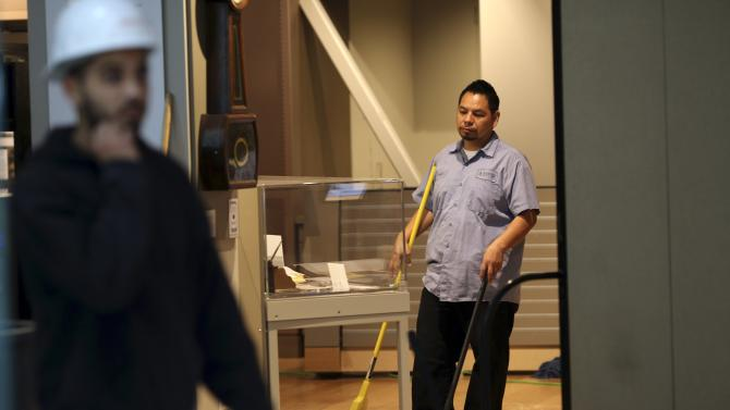 A worker sweeps the damage inside the Wells Fargo History Museum in San Francisco