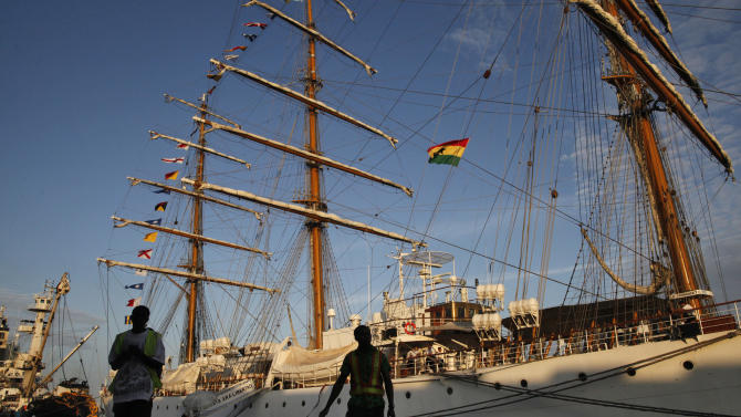 Port workers stand near the three-masted ARA Libertad, a symbol of Argentina's navy, as it sits docked at the port in Tema, outside Accra, Ghana, Saturday, Oct. 20, 2012. Argentina announced the immediate evacuation Saturday of about 300 crew members from the Libertad, a navy training ship seized in Africa nearly three weeks ago as collateral for unpaid bonds dating from the South American nation's economic crisis a decade ago.(AP Photo/Gabriela Barnuevo)