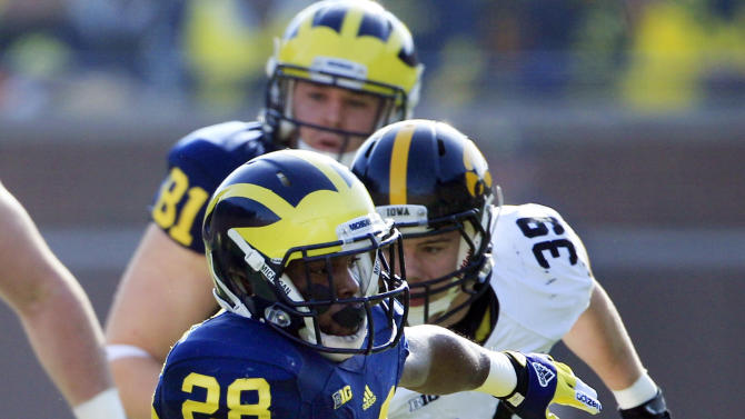 Michigan running back Fitzgerald Toussaint (28) pulls away from Iowa defensive back Gavin Smith (35) during the first quarter of an NCAA college football game at Michigan Stadium in Ann Arbor, Mich., Saturday, Nov. 17, 2012. (AP Photo/Carlos Osorio)