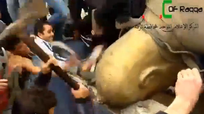 FILE - In this Monday, March 4, 2013 file image taken from video obtained from Ugarit News, which has been authenticated based on its contents and other AP reporting, Syrians attack a fallen statue of former Syrian President Hafez Assad in a central square in Raqqa, Syria. Since Raqqa fell under rebel control last week, opposition fighters have posted guards at government buildings to prevent looting, brought down the price of bread and opened a telephone hotline for residents to report security problems. Raqqa is shaping up as a test case for how rebels will administer their areas.  (AP Photo/Ugarit News via AP video, File)