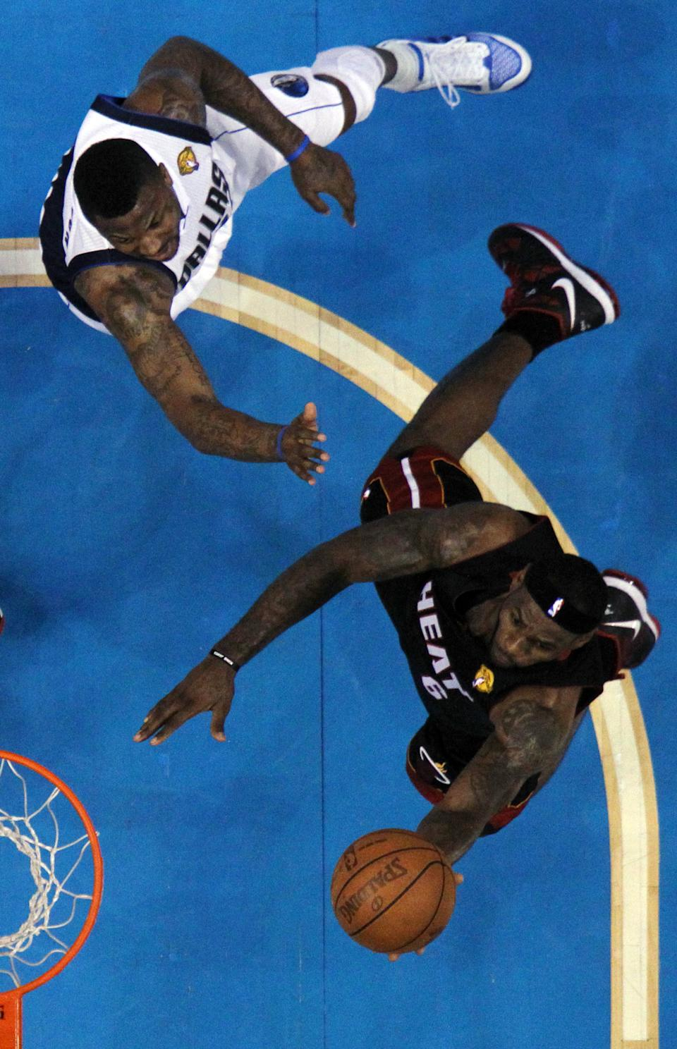 Miami Heat's LeBron James goes up for a shot with Dallas Mavericks' DeShawn Stevenson defending during the first half of Game 5 of the NBA Finals basketball game Thursday, June 9, 2011, in Dallas. (AP Photo/Ronald Martinez; Pool)