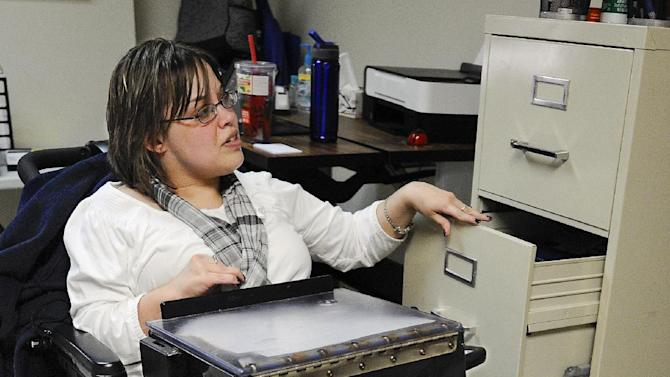 In this photo taken Friday, March 1, 2013, Jennifer Lortie works in her Willimantic, Conn., office. Of the 29 million working–age Americans with a disability Lortie, who has limited arm and leg use due to cerebral palsy, is one of the 5.1 million, who are actually employed. The National Council on Disability's Jeff Rosen says long-standing prejudicial attitudes need to be addressed to boost jobs. (AP Photo/Jessica Hill)