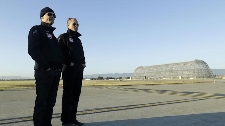 Pilots Bertrand Piccard, left, and André Borschberg watch as the Solar Impulse landed after a test flight at Moffett Field NASA Ames Research Center in Mountain View, Calif., Friday, April 19, 2013. A solar-powered plane that has wowed aviation fans in Europe is set to take an early morning test flight over the San Francisco Bay area. Considered the world's most advanced sun-powered plane, the Solar Impulse is set to take off from Moffett Field in Mountain View at first light for a two-hour practice run leading up to the start of a multi-city, cross-country tour. (AP Photo/Jeff Chiu)