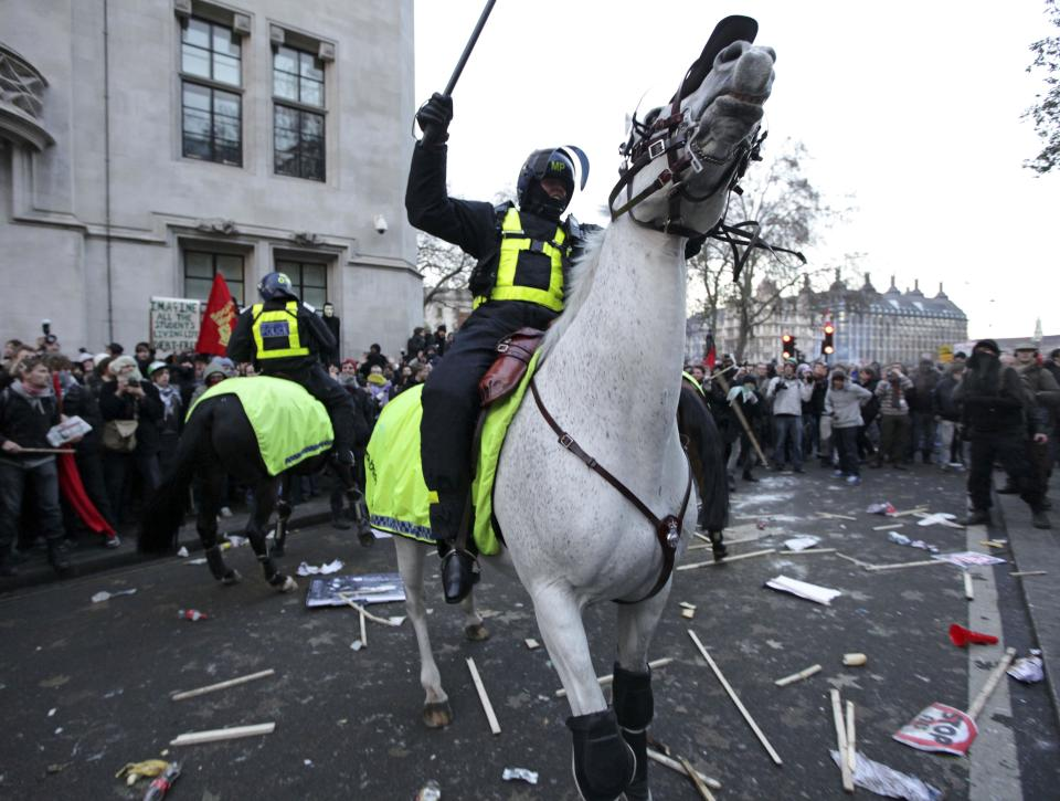 A mounted police officer pushes protesters back during a protest against an increase in tuition fees on the edge of Parliament Square in London, Thursday, Dec. 9, 2010.  Police clashed with protesters marching to London's Parliament Square as lawmakers debated a controversial plan to triple university tuition fees in England.  (AP Photo/Matt Dunham)