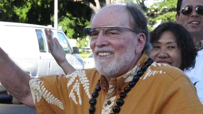 Hawaii Gov. Neil Abercrombie wears Google Glass as he waves at passing cars during a campaign event in Honolulu on Tuesday, Aug. 5, 2014. Abercrombie faces a tight re-election battle in a primary against state Sen. David Ige. (AP Photo/Oskar Garcia)