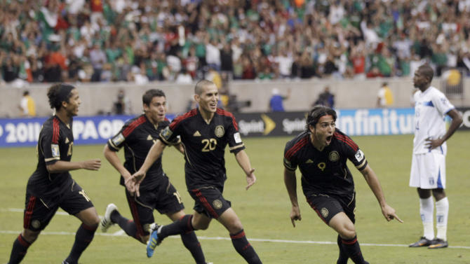 Mexico's Aldo De Nigris celebrates his goal with teammates as Honduras' Oscar Boniek Garcia stands nearby during overtime of a CONCACAF Gold Cup semifinal soccer match Wednesday, June 22, 2011, in Houston. (AP Photo/David J. Phillip)