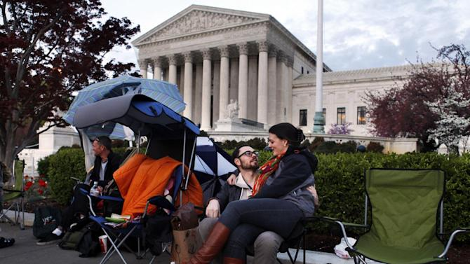 """Monica Haymond, right, sits with her boyfriend Dana Stuster, both recent transplants to Washington from Pasadena, Calif., as they wait in line for tickets to the Supreme Court on the eve of the Supreme Court arguments on President Obama's health care legislation, in Washington, on Sunday, March 25, 2012. """"We're going to wait to enter until Tuesday,"""" says Haymond, a legal assistant who has been in line since Friday, """"since that's when they'll discuss the individual mandate. They'll be talking about unprecedented things, it's going to be historic."""" (AP Photo/Jacquelyn Martin)"""