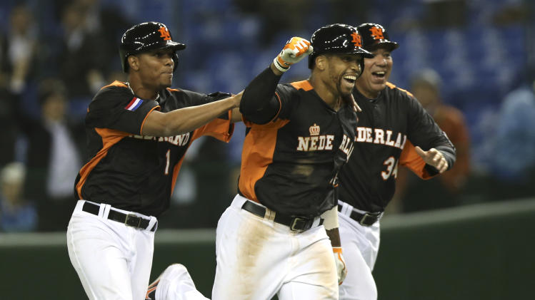 Netherlands' centerfielder Kalian Sams, center, celebrates with teammate Xander Bogaerts, left, and coach Wirn Martinus after hitting a walk-off sacrifice fly to beat Cuba 7-6 in their World Baseball Classic second round game at Tokyo Dome in Tokyo, Monday, March 11, 2013. (AP Photo/Toru Takahashi)