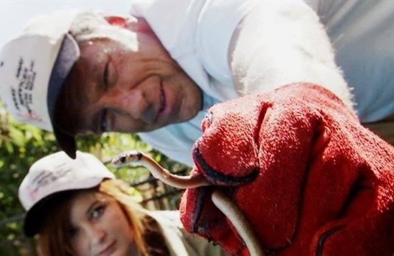 "Mike Rowe shows off a snake on an episode of ""Dirty Jobs."""