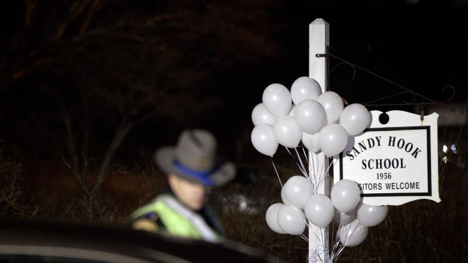 White balloons decorate the sign for the Sandy Hook Elementary School as a Connecticut State Trooper stands guard at the school's entrance, Saturday, Dec. 15, 2012, in Newtown, Conn. A gunman killed his mother at their home and later walked into Sandy Hook Elementary School Friday and opened fire, killing 26 people, including 20 children. (AP Photo/David Goldman)