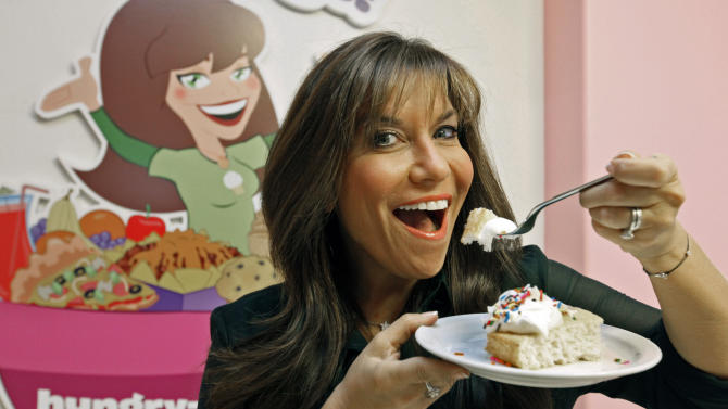 """In this Oct. 11, 2012 photo, """"Hungry Girl"""" Lisa Lillien poses in her office in the Woodland Hills area of Los Angeles. She never set out to become a controverisal food maven, telling people how to eat their cake and keep their weight down too. Lillien was just another LA """"Hungry Girl,"""" a 30-something woman who would diet off that extra 20 pounds and then put the weight back on. That was until the former studio publicist started coming up with low-cal recipes for some of those favored foods and emailing them around to friends. Ten years later, Lillien sits atop a Hungry Girl empire. ( AP Photo/Nick Ut)"""