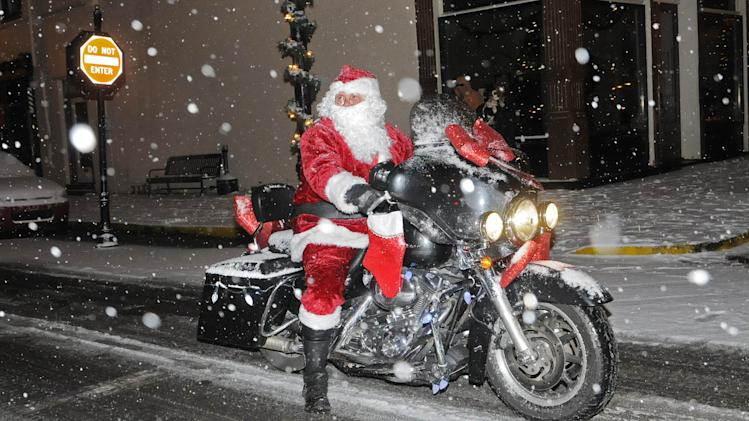 Santa rides his motorcycle along the route of the Twilight Christmas Parade Friday, Dec. 6, 2013 in Maysville, Ky during a steady snowfall. Alan Henderson was portraying Santa Claus. (AP Photo/The Ledger Independent, Terry Prather).