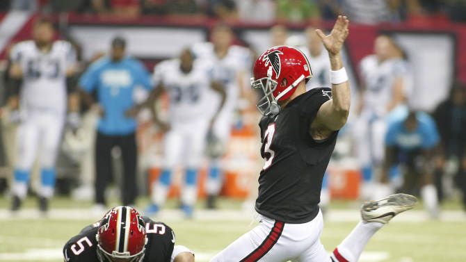 Falcons Bosher holds the ball for Bryan who makes the winning field goal kick against the Panthers in their NFL football game in Atlanta