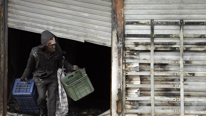 A man leaves a burnt shop owned by a foreign national in Johannesburg, South Africa, Sunday, April 19, 2015. South Africa's president on Saturday canceled a foreign trip in order to deal with a wave of attacks on immigrants that have killed at least six people. (AP Photo/Themba Hadebe)