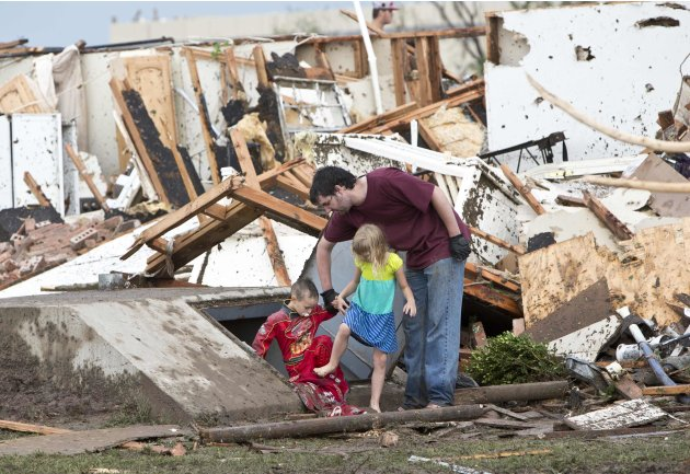 A man and two children exit a shelter after debris was cleared from on top, after a huge tornado struck Moore, Oklahoma