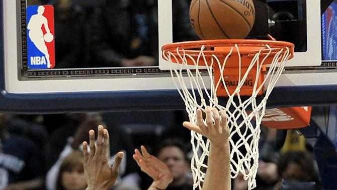 Memphis Grizzlies center Marc Gasol scores against Houston Rockets center Dwight Howard (12) during the first half of an NBA basketball game Friday, Dec. 26, 2014, in Memphis, Tenn. (AP Photo/Brandon Dill)