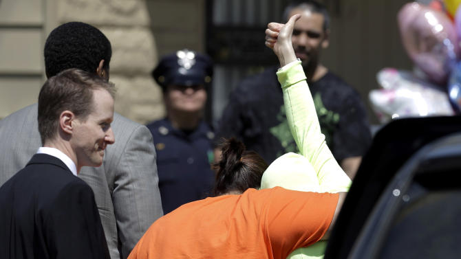 FILE - In this Wednesday, May 8, 2013 file photo, Gina DeJesus gives a thumbs-up as she is escorted toward her home in Cleveland. For DeJesus, Amanda Berry and Michelle Knight, who were freed from captivity inside a Cleveland house on Monday, May 6, the ordeal is not over. Next comes recovery _ from sexual abuse and their sudden, jarring reentry into a world much different than the one they were snatched from a decade ago. (AP Photo/Tony Dejak, File)